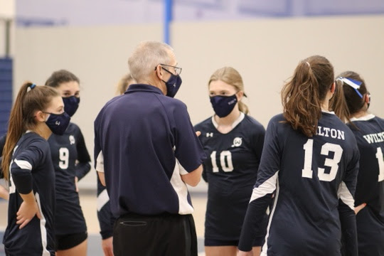 Coach Liptack huddles with his team during a match, following with a motivating speech.