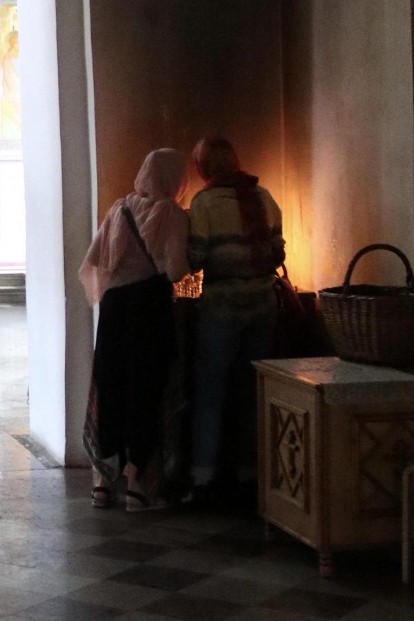 Simakova stands with her mother, lighting a candle in remembrance of those they care about.